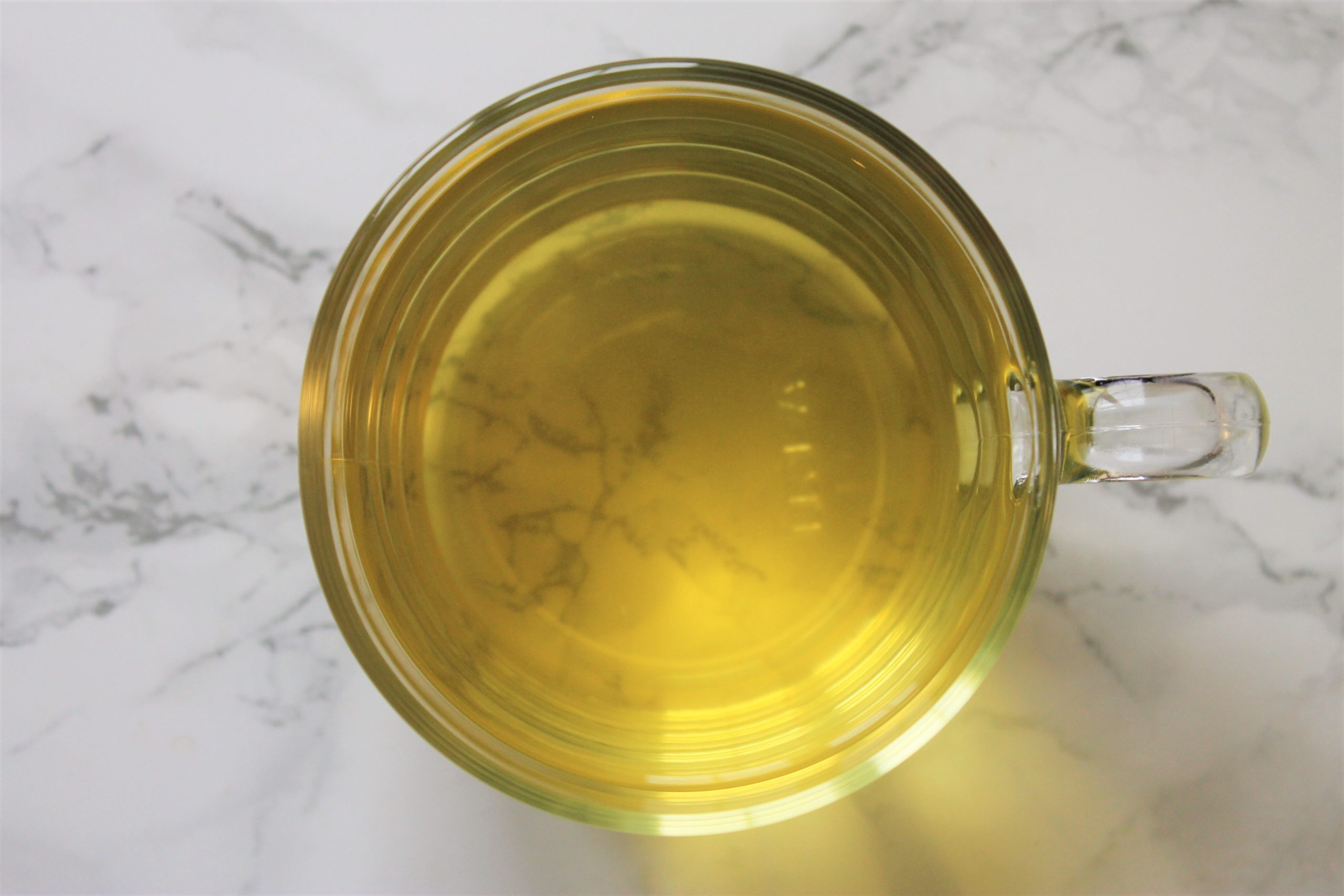 yellow tea chamomile in glass teacup on marble
