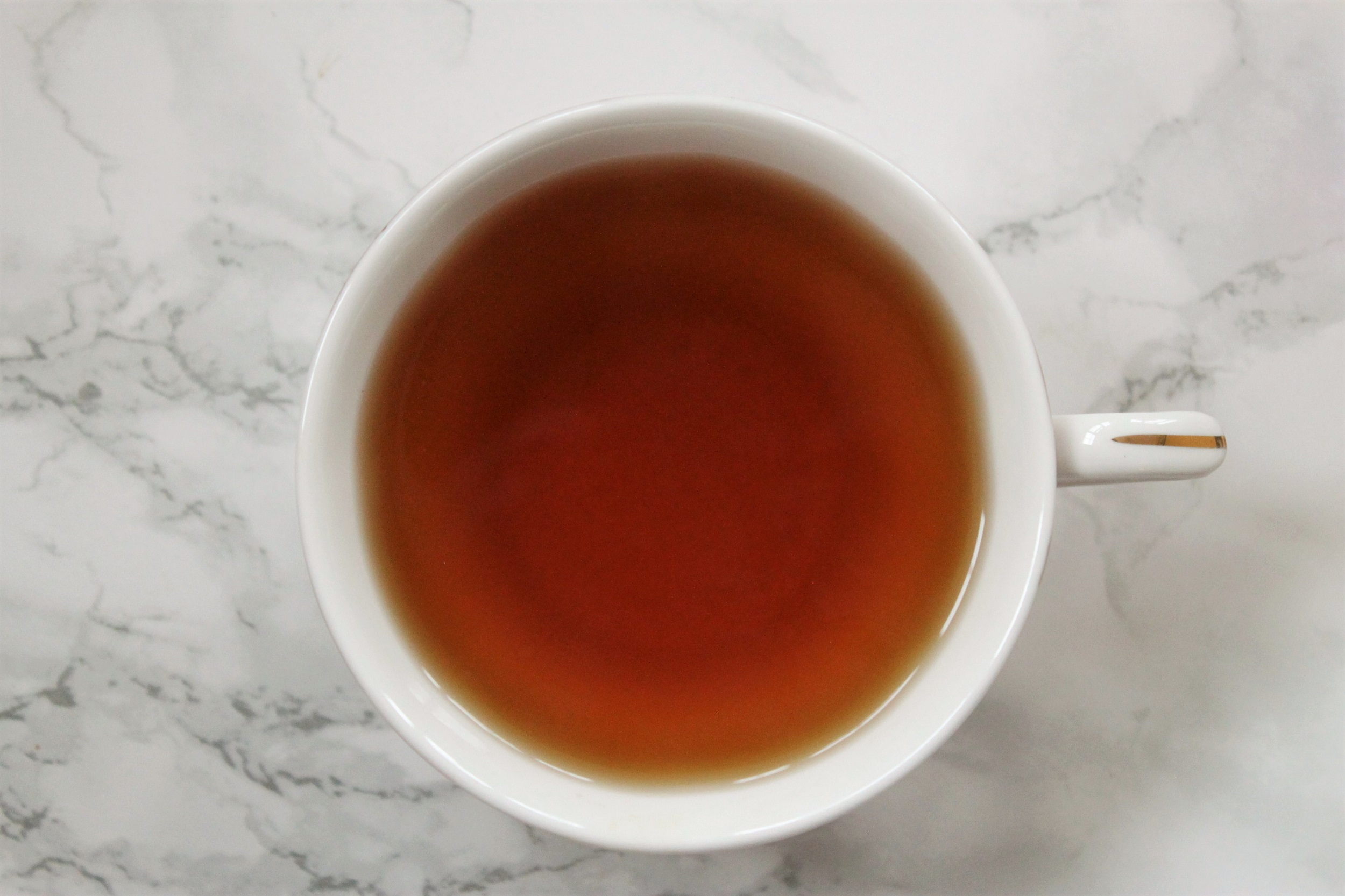brown cinnamon tea in white teacup
