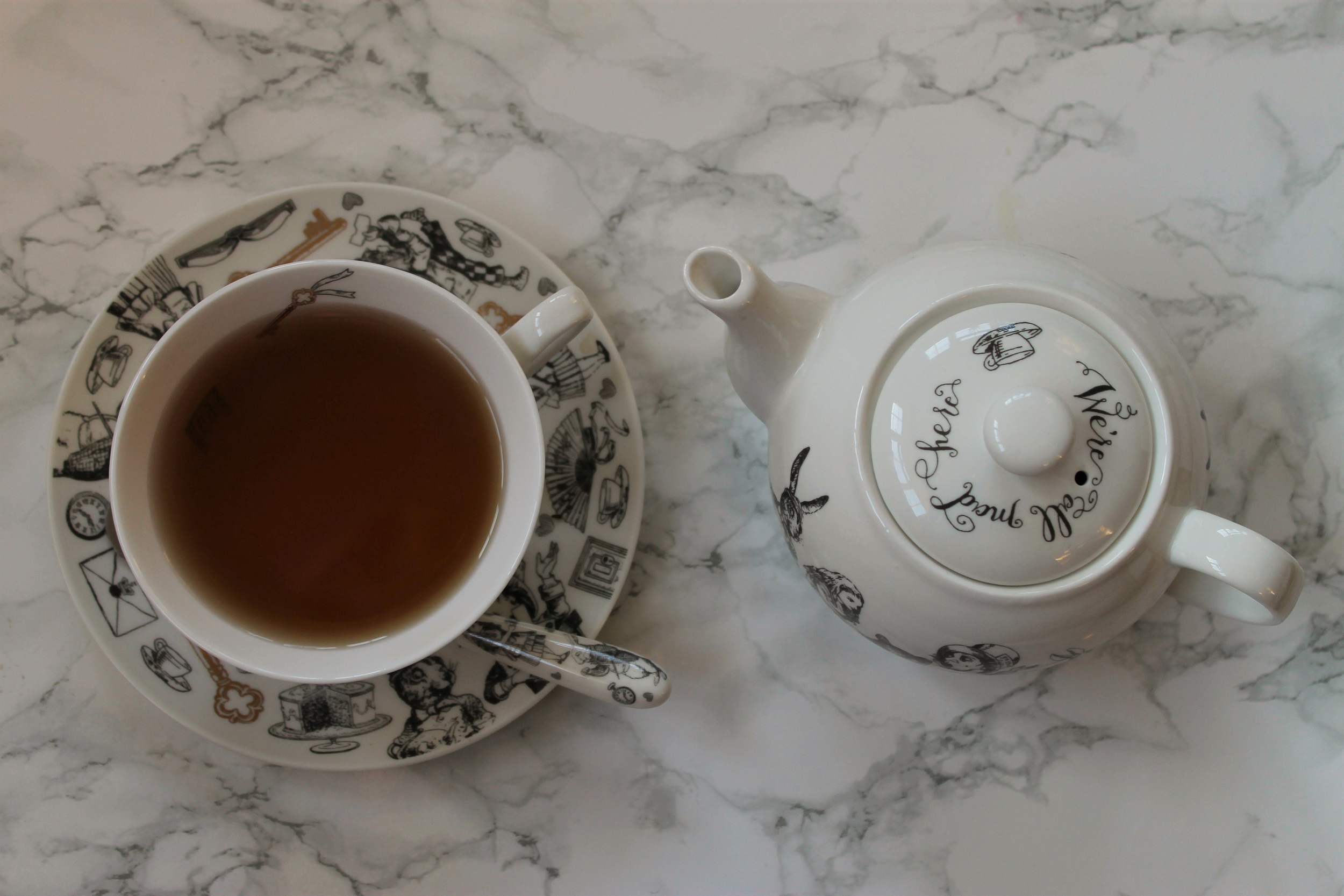 alice in wonderland teapot and teacup with black tea