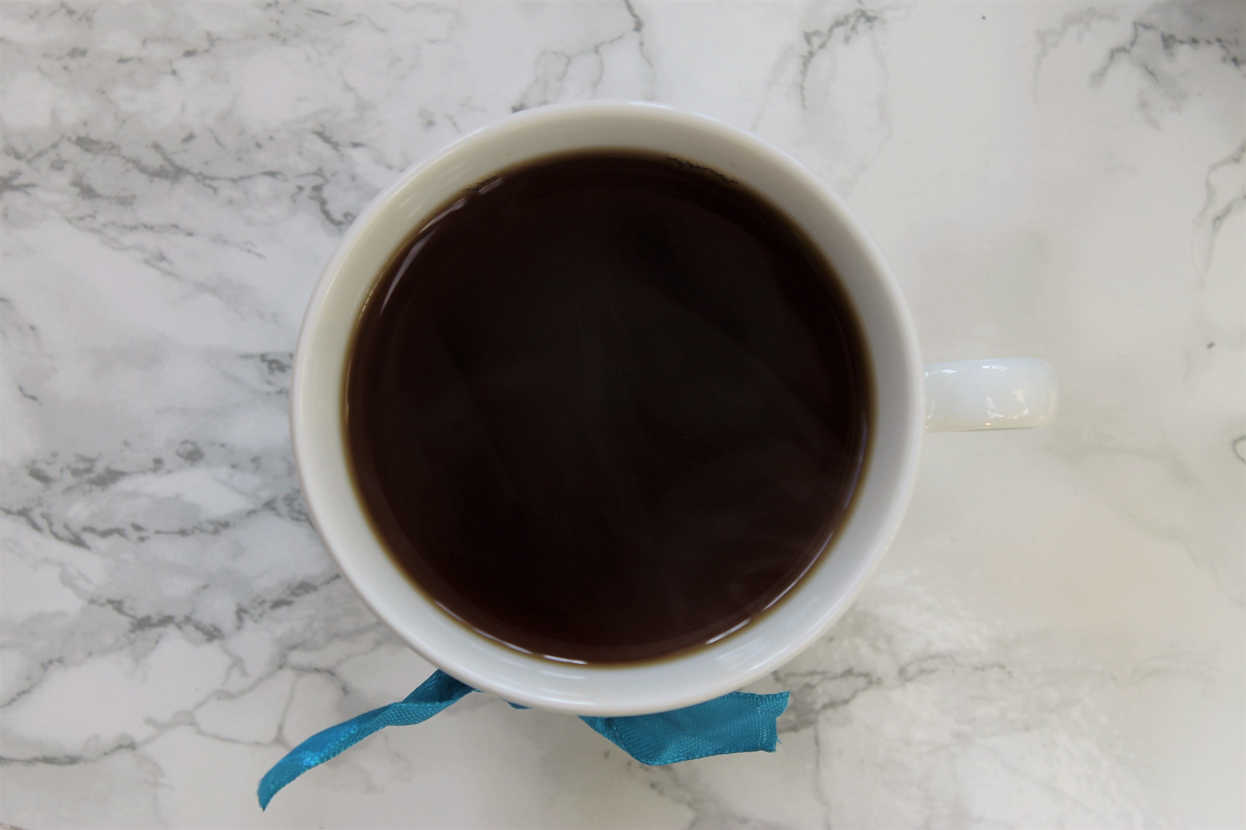 black tea in white tea cup with blue ribbon