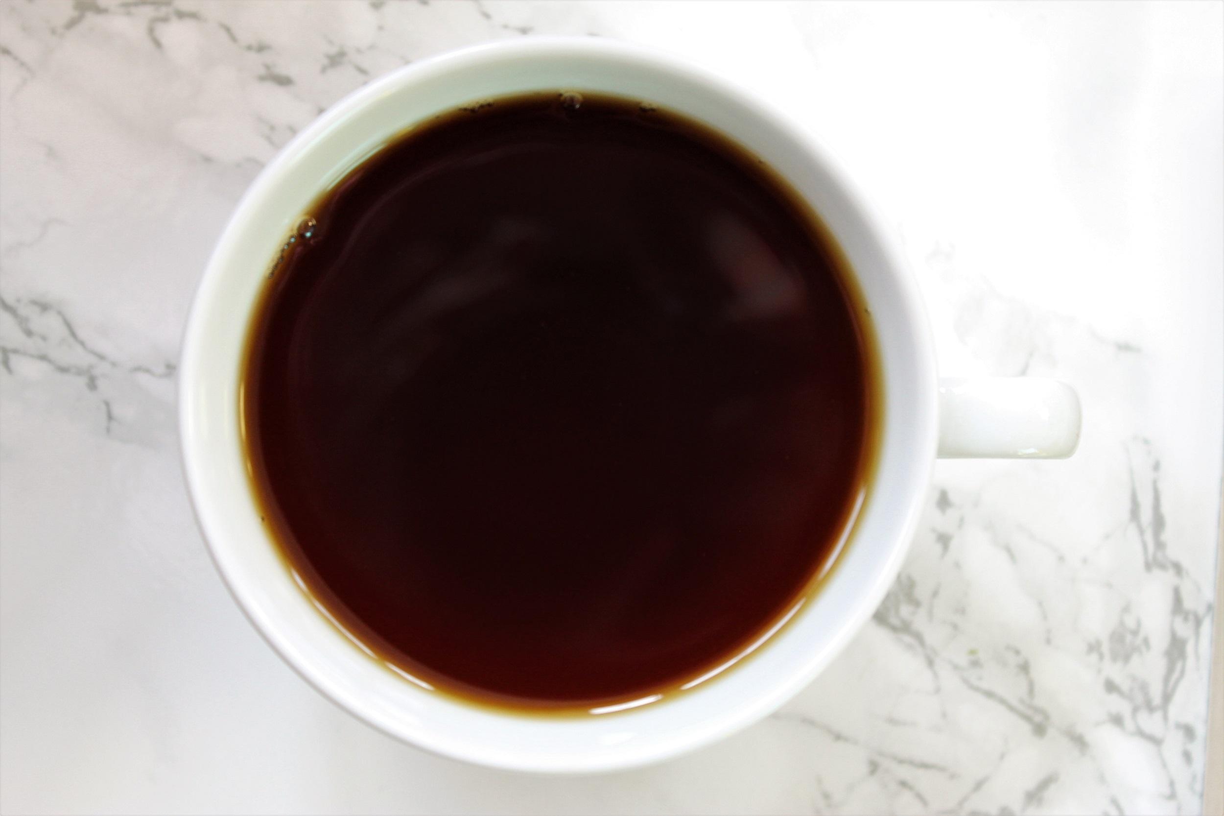black brown tea in white teacup on marble