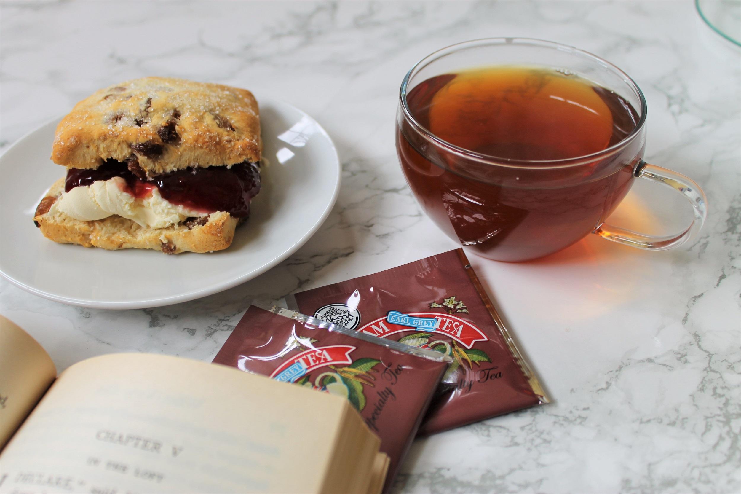 cream tea scone with book and black tea in teacup